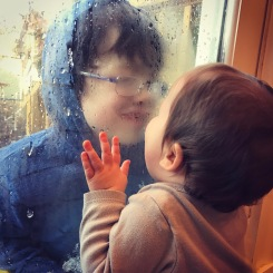 Kissing her brother through the glass